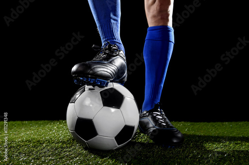legs and feet of football player in blue socks and black shoes posing with the ball playing on green grass