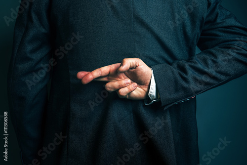 Lying businessman holding fingers crossed behind his back