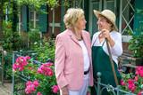 Two Senior Women Talking Together in Garden. - 111326352