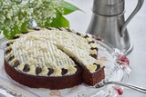 chocolate cake on cake stand with lily of the valley and cake spoon
