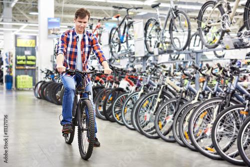 Man vérifie vélo avant d'acheter dans la boutique Poster