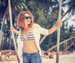 beautiful young woman on a swing on the shore of tropical sea