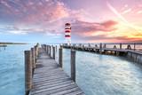 Steg mit Leuchtturm am Seeufer, Sonnenuntergang