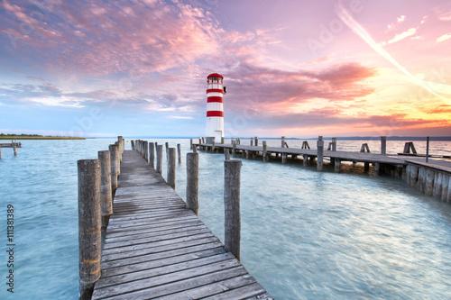 Steg mit Leuchtturm am Seeufer, Sonnenuntergang - 111381389