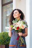 Happy charming young woman florist holding flower bouquet near shop