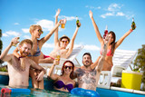 Young people having fun in pool with drinks in arms