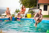 Tattooed man jump bomb style in pool