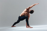Handsome man doing yoga exercise - 111396381