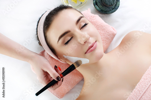 Woman with clay facial mask in beauty spa. плакат
