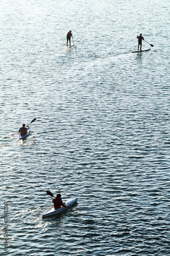 people  practicing kayaking and stand up paddle board in the sea - 111402561
