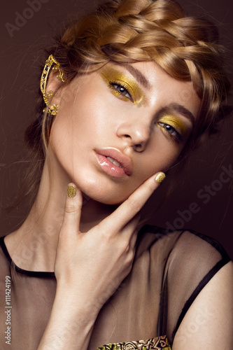 Poster Beautiful girl in a gold dress with creative makeup and braids on her head