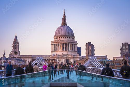 Fototapeta Londoners walking through Millennium Bridge after sunset - London, UK