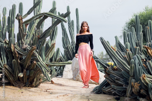 Poster Hippie woman in long pink skirt walking near big cactuses