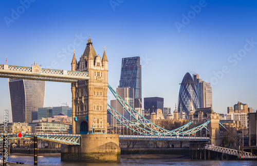 Fototapeta London, England - Iconic Tower Bridge in the morning sunlight with Bank District at background