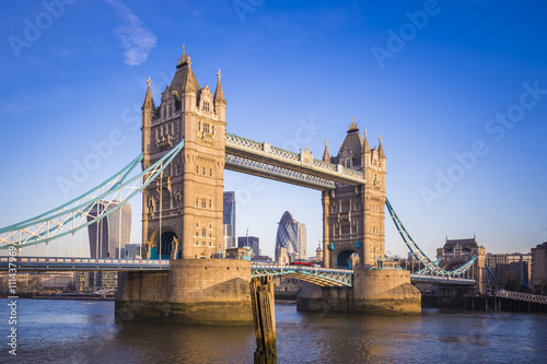 Fototapeta London, England - Iconic Tower Bridge in the morning sunlight with Red Double Decker bus and Bank District at background