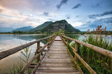 boardwalk that crosses the lake towards the mountains at sunset