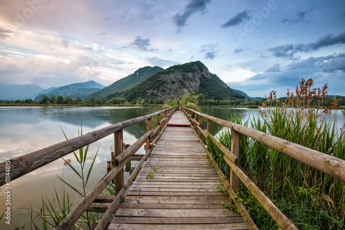 boardwalk that crosses the lake towards the mountains at sunset - 111448156