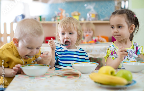 group of children eating from plates in day care centre Poster