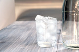 Fresh pure water with ice cubes in a glass and bottle on a wooden table.