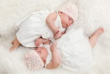 Cute twin sisters, newborn babies lying together in white dresses