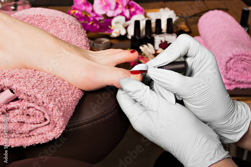 Plagát, Obraz Closeup finger nail care by pedicure specialist in beauty salon.