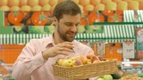 Happy man choosing fresh apricots In supermarket