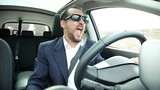 Happy cool business man with sun glasses dancing in car