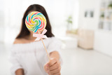 Young woman covering her face with lollipop, selective focus