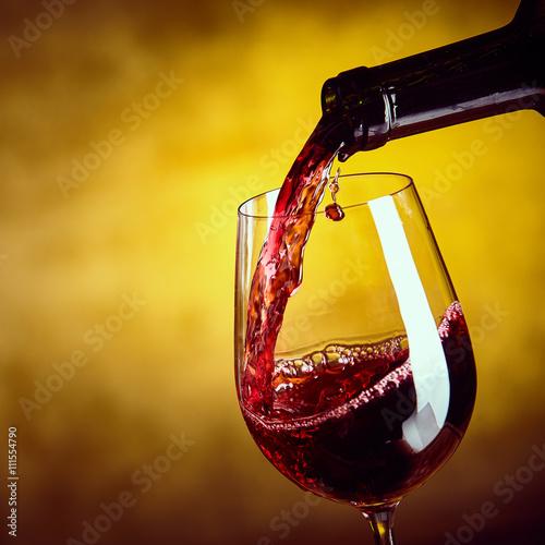 Fototapeta Dispensing red wine from a bottle