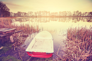 Vintage toned boat by a lake at sunrise © MaciejBledowski