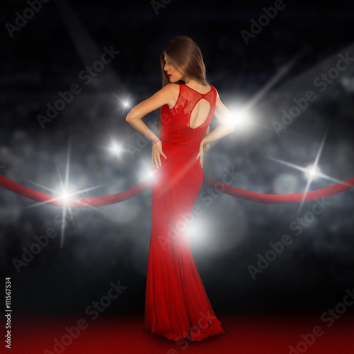 Poster lady on red carpet is posing in paparazzi flashes
