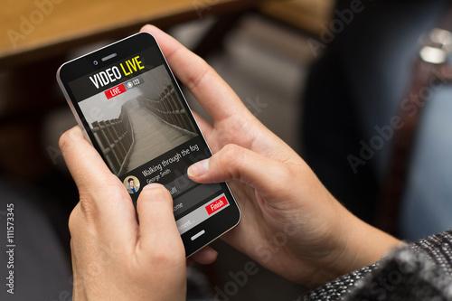 Rue fille regarder une vidéo en direct avec un smartphone Poster