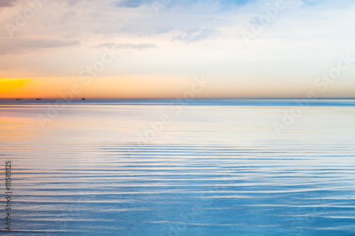 Still blue sea water under colorful sky - 111588125