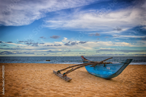 Old blue fishing boat on sandy beach