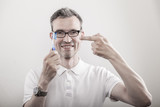 Zahnarzt zeigt mit dem Zeigefinger auf eine blau weisse Zahnbürste