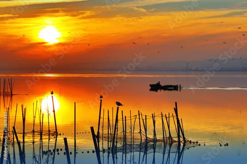 obraz lub plakat puesta de sol sobre el agua