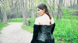 Young renaissance woman walking down path in forest on sunny day.