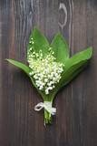 lilies of the valley bouquet on dark wooden background