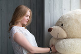 Beautiful girl hugging a teddy bear. Blonde woman posing in the studio