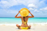 Summer beach vacation carefree happy woman relaxing enjoying sun holiday in tropical destination. Perfect paradise happiness. Back view of bikini girl holding yellow fashion hat on Caribbean holiday.