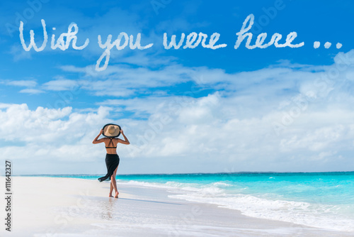 Poster Wish you were here cloud message written in sky above woman walking on beach vacation Luxury travel Caribbean destination