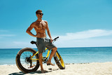 Fitness Male Model With Bike Sunbathing On Sun, Enjoying Summer Travel Vacation. Handsome Sexy Man In Sunglasses With Muscular Body, Healthy Tan Skin Tanning Near Bicycle On Sand Beach. Summertime  - 111680353
