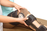 Orthopedist secures leg brace on knee, knee brace support for le
