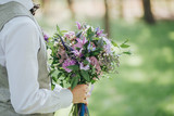 groom holding a wedding bouquet of flowers and greenery