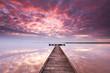 Licht durchbricht die Wolken, Sonnenaufgang am See mit Steg