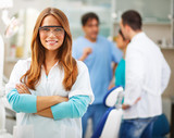 Young female dentist standing in his office and looking at camera.