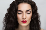 Portrait of beautiful young girl, woman, lady, model. Flawless makeup, perfect shape of the eyebrows, long eyelashes, bright red lipstick. Image can be used for advertising of cosmetic products.