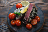 Tuna steak roasted in sesame seeds with cherry tomatoes