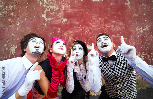 Four mimes point to the top on a red wall. Poster