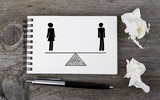Equality of man and woman. On a wooden table notebook